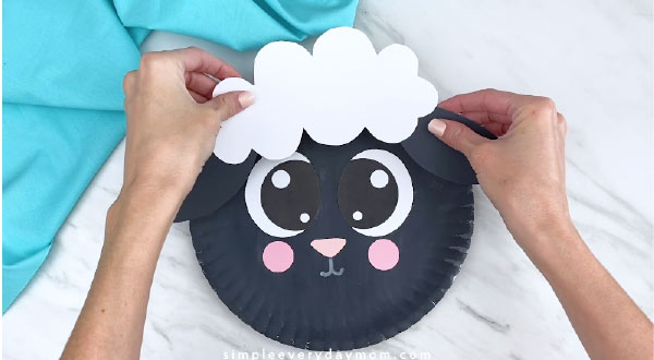 Hands gluing sheep fluff and ears to paper plate