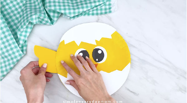 Hands gluing wings to paper plate chick