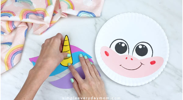 hands gluing unicorn horn to colorful hair