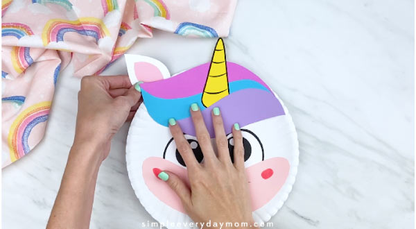 hands taping finished unicorn ear to back of paper plate unicorn