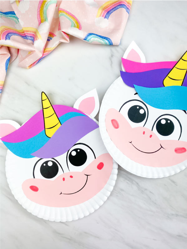 closeup of two paper plate unicorns