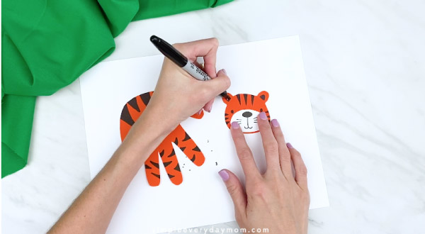 hands coloring in tiger ears with black marker