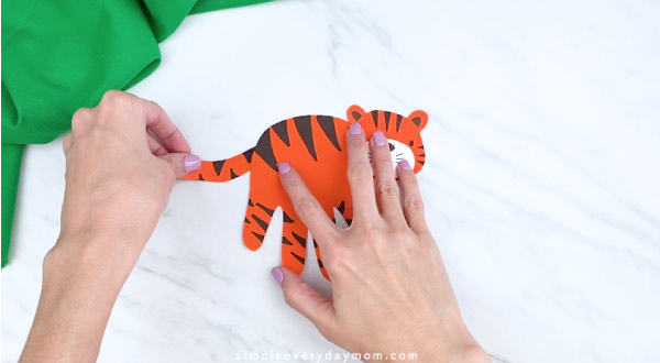hands gluing on tail to handprint tiger craft