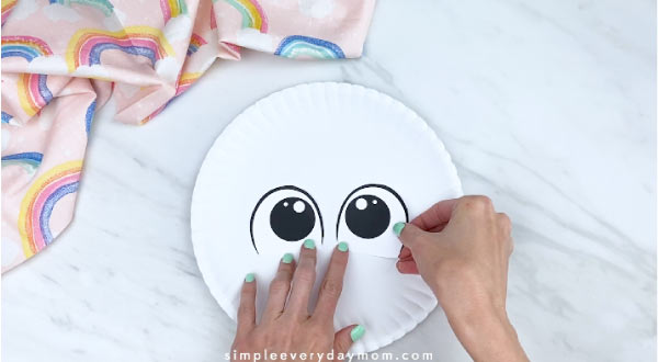 hands gluing on eyes to white paper plate