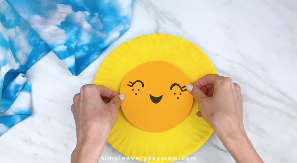 hands gluing on face to paper plate sun