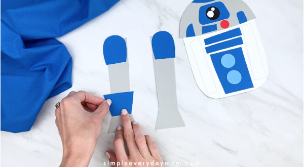 hands gluing base of leg to R2D2 craft