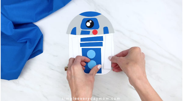 hands placing decorations on paper r2d2 craft