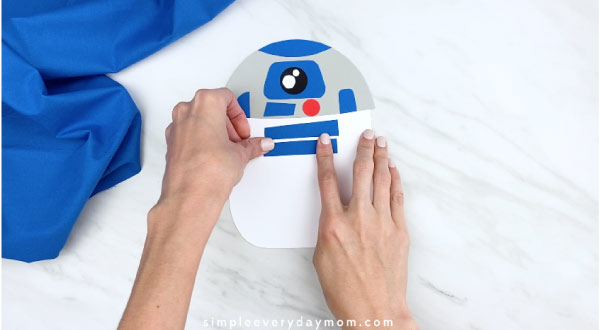 hands gluing on blue rectangles onto R2D2