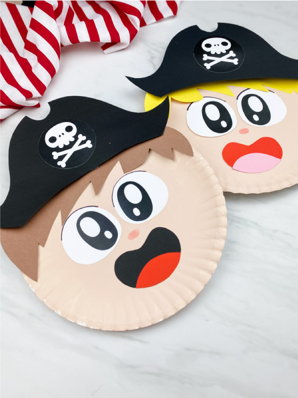 brown haired paper plate pirate craft on marble background with red and white striped fabric