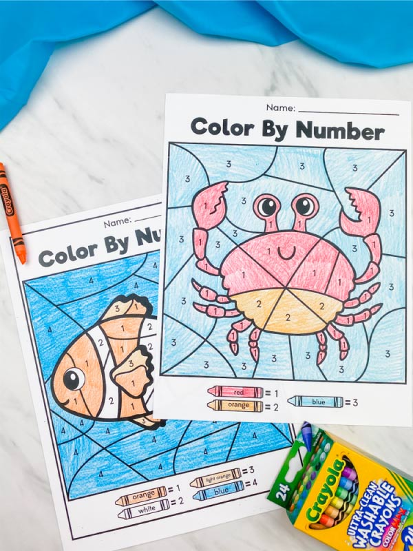 crab and clownfish color by number with orange crayon and box of crayons