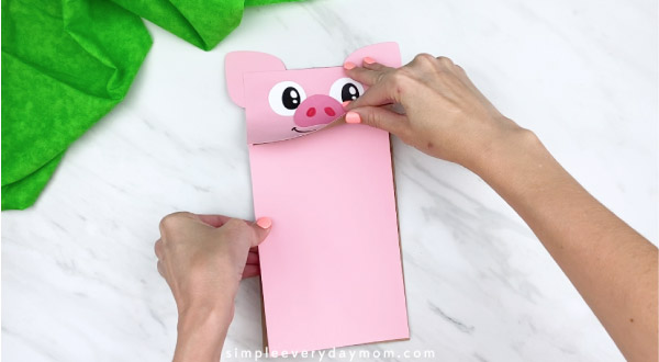 hand gluing pink paper onto paper bag puppet craft