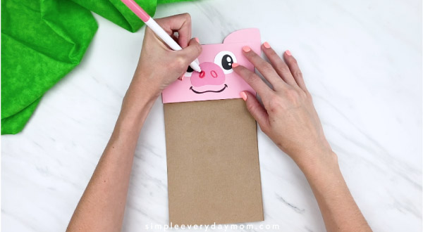 hands drawing on nostril hole on paper bag pig craft with pink marker