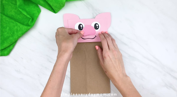 hands gluing on nose on paper bag pig craft