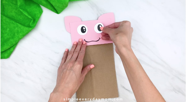 hands gluing on eye to paper bag pig craft