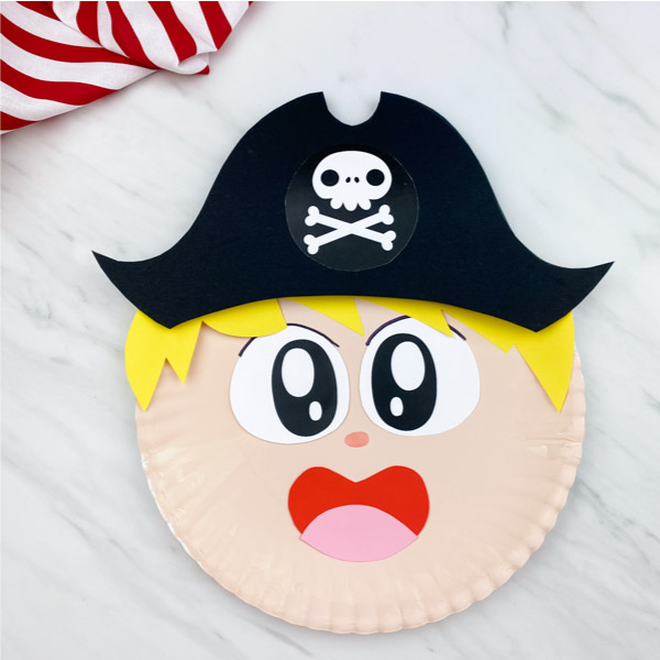 paper plate pirate craft on marble background with red and white striped fabric