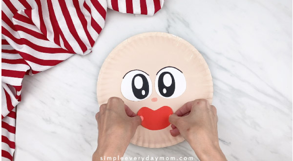 hands gluing on red mouth to paper plate pirate