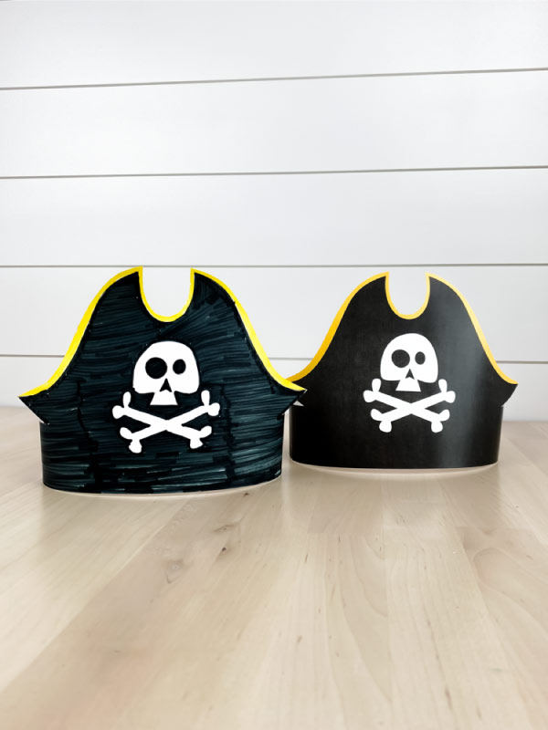 two paper pirate headbands on wood table