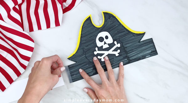 hand taping together paper pirate headband