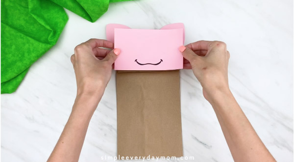 hand gluing on paper bag pig face