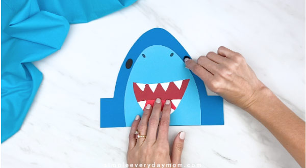 hands gluing on shark eyes