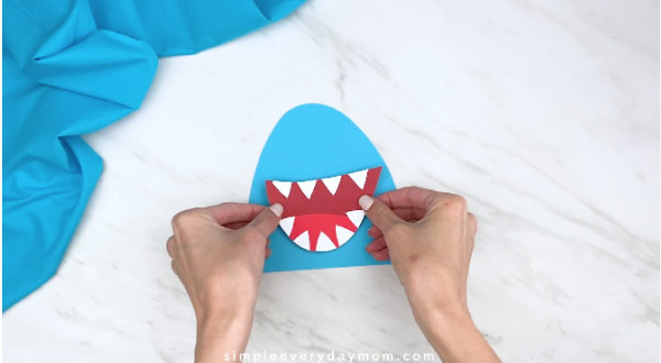 hands gluing onto mouth to shark head