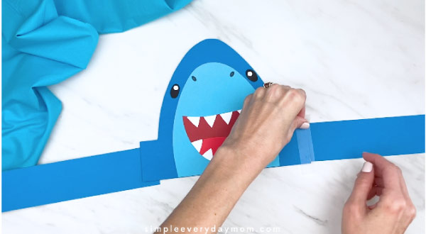 hands taping shark headband together