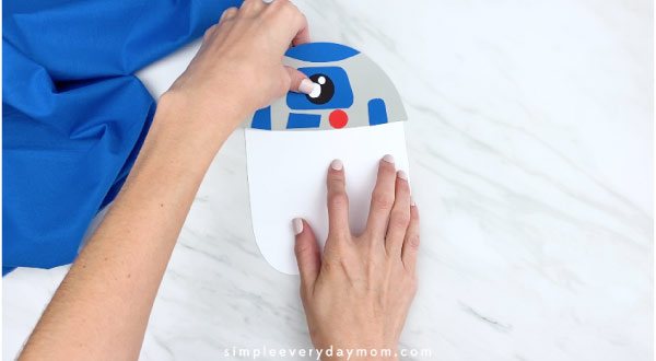 hands gluing on white body for R2D2