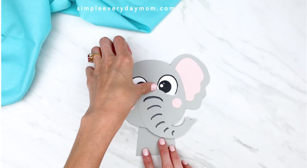 hands gluing head onto elephant paper craft body