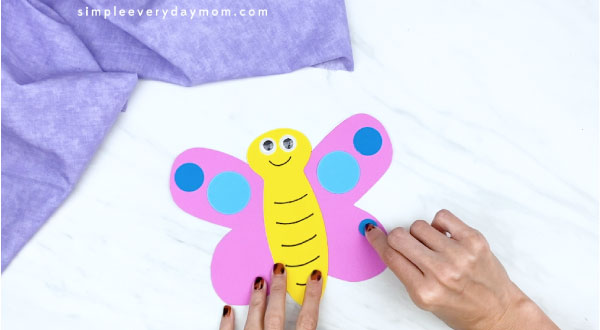 hands gluing on blue circle to butterfly card craft