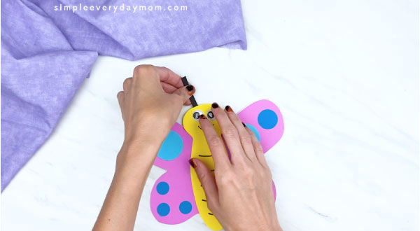 hands gluing on black antenna to paper butterfly craft