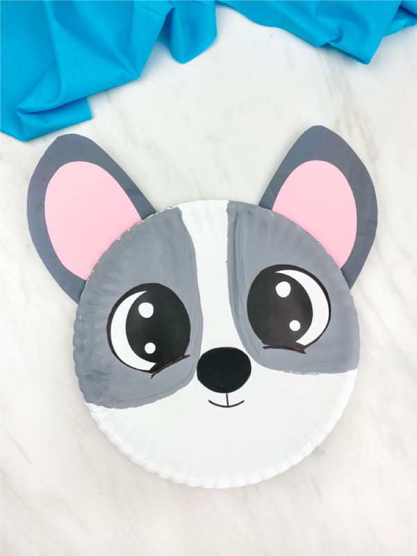 gray paper plate dog craft on marble background with blue fabric