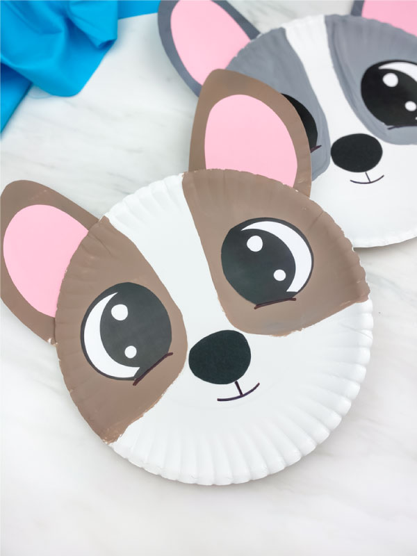 closeup of brown paper plate dog craft with gray paper plate dog craft in background