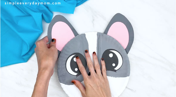 hands gluing completed ears to back of paper plate dog craft