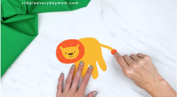 hands gluing on lion tail hair to craft