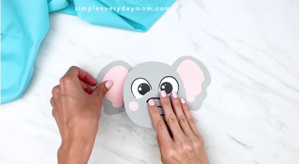 hands gluing ears onto elephant paper craft