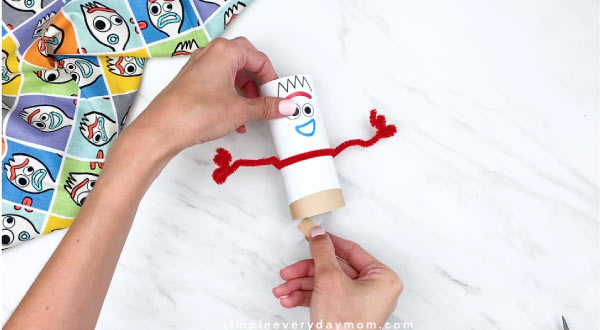 hands gluing on Forky feet to Forky craft
