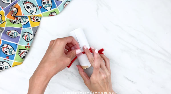 hands taping down red pipe cleaner to Forky body