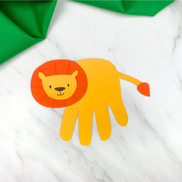 handprint lion craft on marble background with green fabric