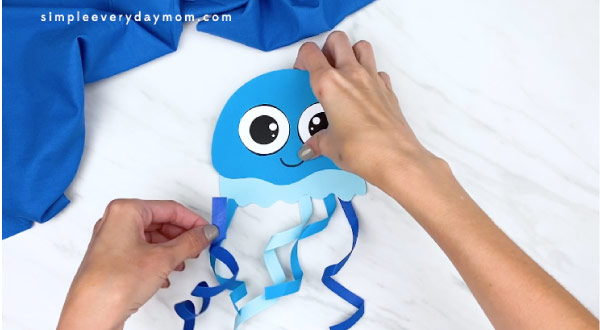 hands gluing curled ribbon onto jellyfish