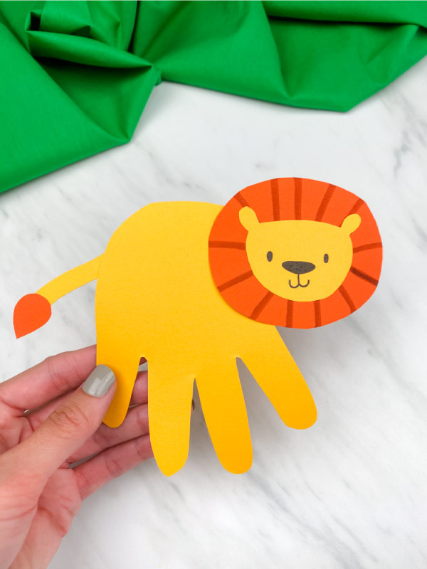 hand holding handprint lion craft with marble background and green fabric