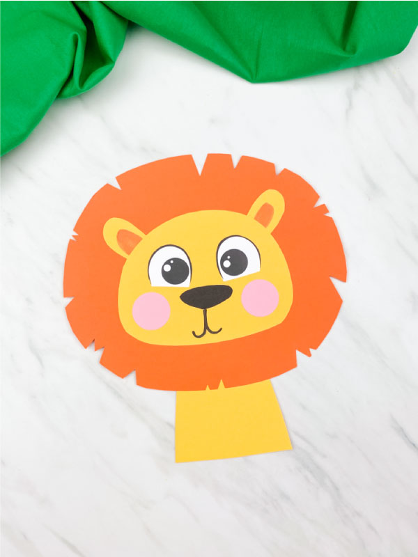 paper lion craft with dark orange mane on marble background with green fabric