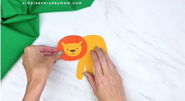 hands gluing on lions face and mane to handprint lion body