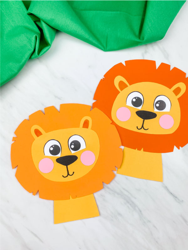 light orange maned and dark orange maned paper lions on marble background with green fabric