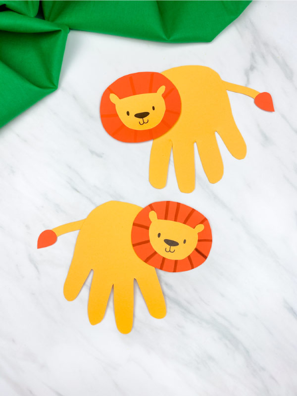 two handprint lions placed vertically with on marble background with green fabric