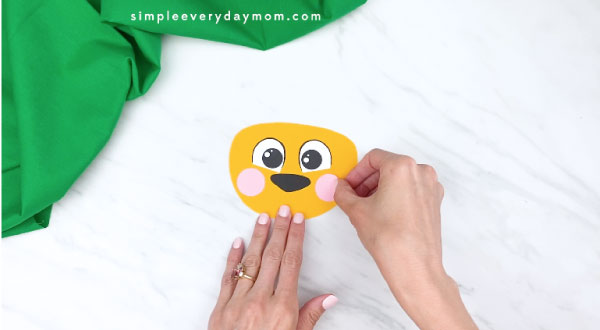 hands gluing on cheeks to paper lion craft