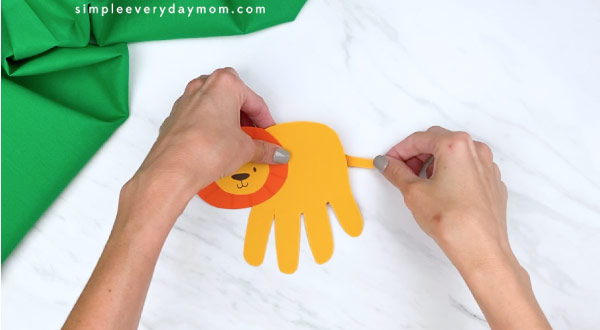 hands gluing on tail to handprint lion