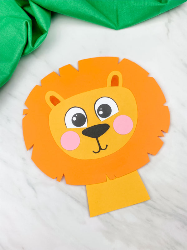 paper lion craft with light orange mane on marble background with green fabric