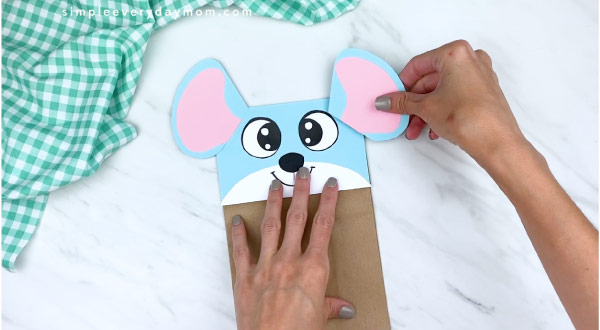 hands gluing completed ear to paper bag mouse