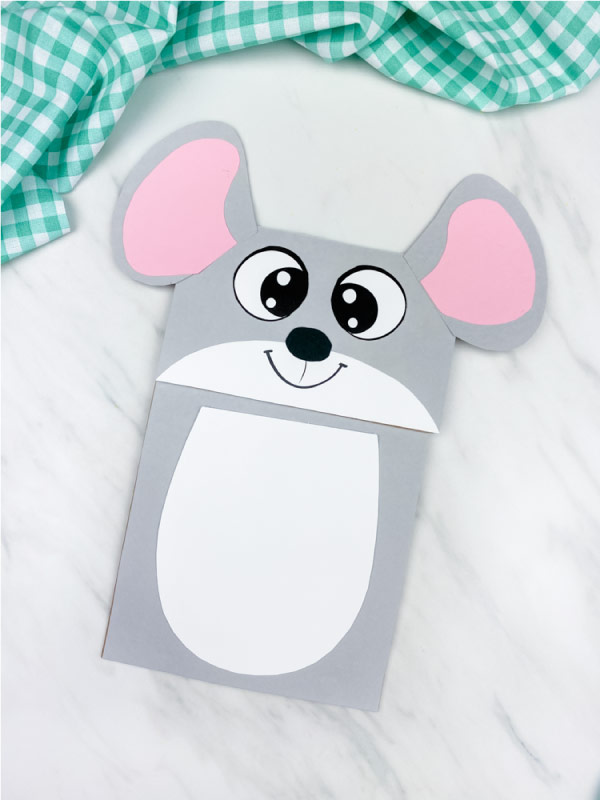 gray paper bag mouse craft on marble background with green checkered fabric