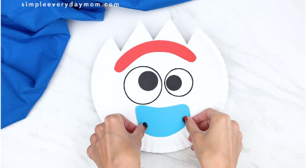 hands gluing on bottom part of Forky's mouth